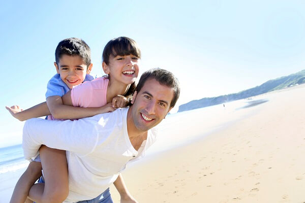 A dad playing with his son and daughter at the beach