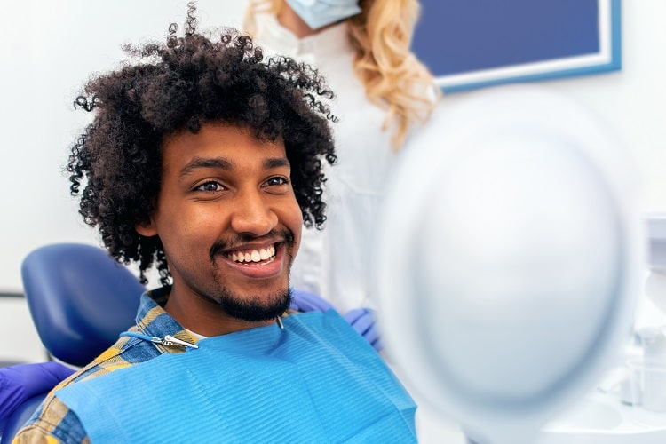 Man in a dental chair checking his smile in a mirror