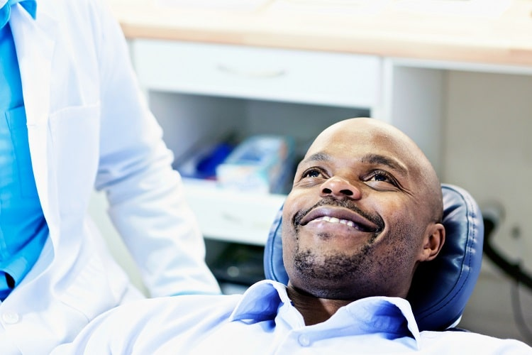 A male patient reclining in a dental chair ready for his restorative dentistry appointment