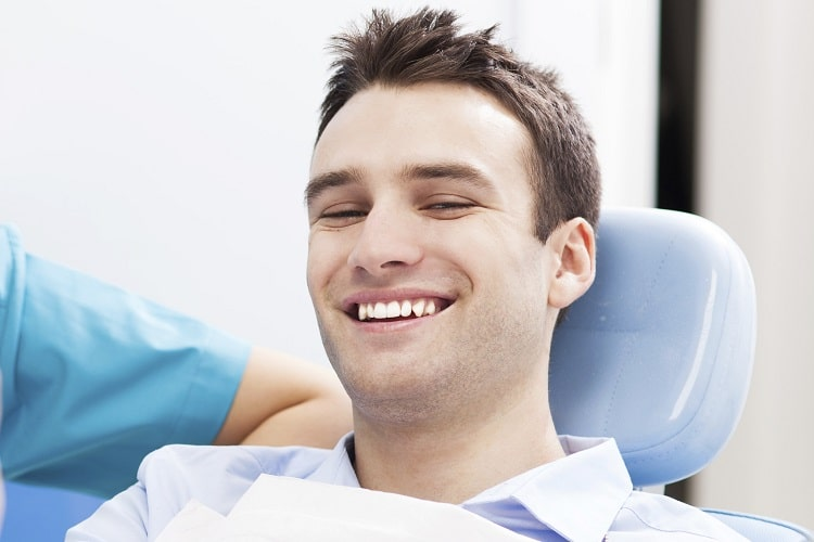 A male patient smiling with his new dental implants