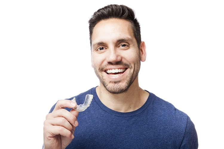 A man in a blue shirt putting on his mouthguard