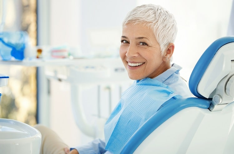 An older woman in a dental chair with a perfect smile thanks to her new dentures