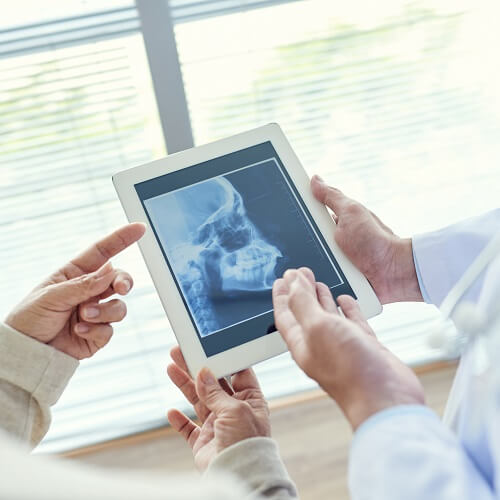 A dentist showing a patient their x-rays on a tablet