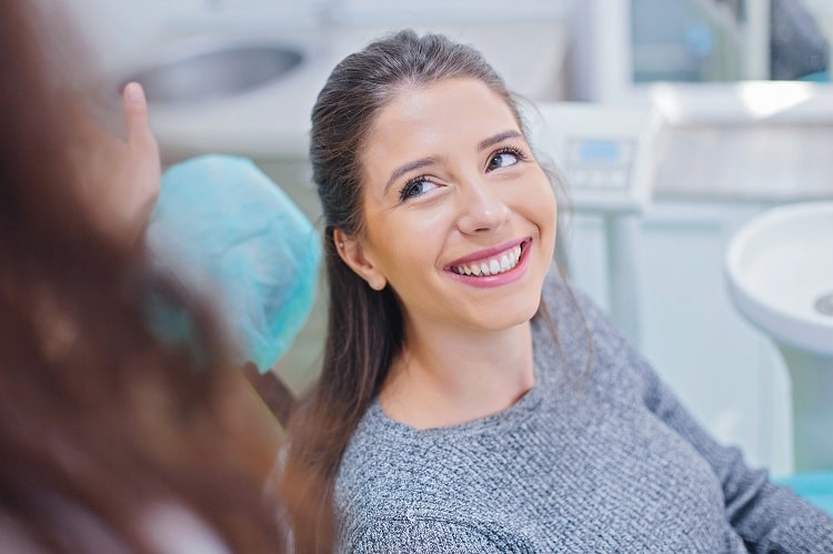 A woman smiling up at her cosmetic dentist