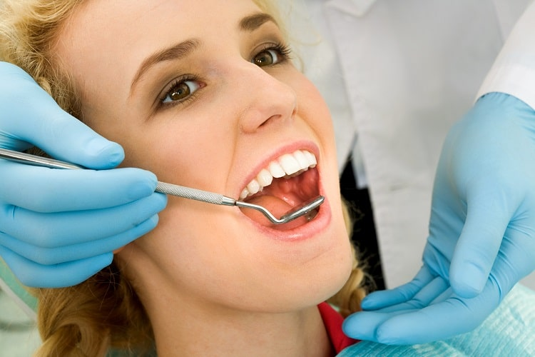 A female patient in the middle of a dental exam