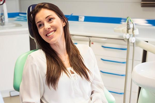 A female patient smiling while receiving BioRejuvenation Dentistry
